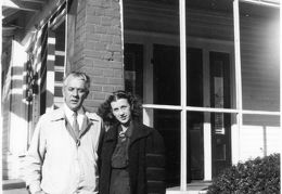 couple by a house with a bicycle - Brantley pics - dated 24 Nov 1947